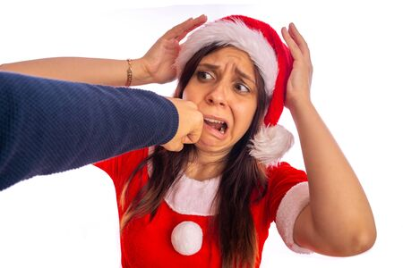 Man is beating frightened woman in suit of Santa Clause in face with fist. Stock fotó