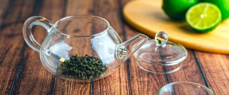 A glass teapot with tea leaves inside on a wooden table