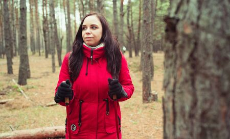 A pretty young woman is engaged in the nordic walking in woods