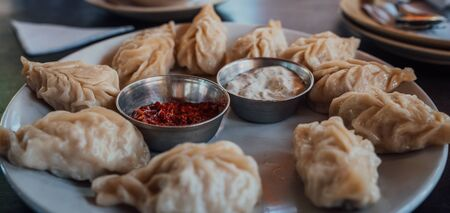 A dish of the tibetan boiled momo with a sauce. Momo is a dish of dough with a filling