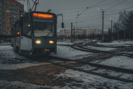 Modern tram in winter city in evening. Contemporary tram is on tram station in cloudy day in countryside