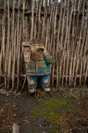 Wooden gnome near wooden fence on ground. Old cracked figure carved from wood. Garden gnome in countryside