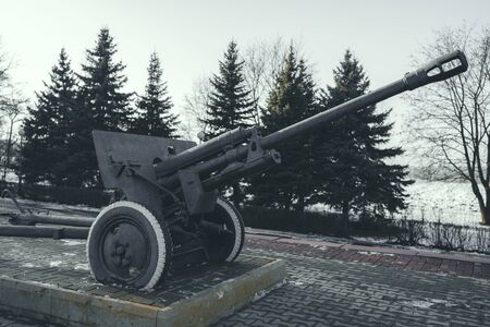 Old anti tank cannon monument mounted on pedestal on winter day in military park