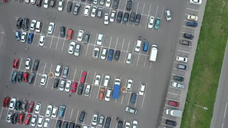 A view from above to the process of car parking. Heavy traffic in the parking lot. Searching for spaces in the busy car park.