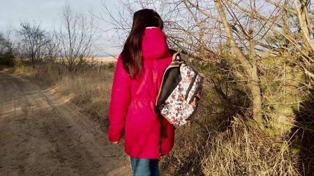 Back view of young female with colorful backpack getting down on path of countryside in spring day