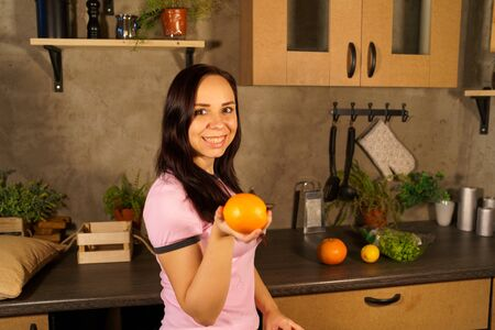 Portrait of charming female holding oranges in her hands.