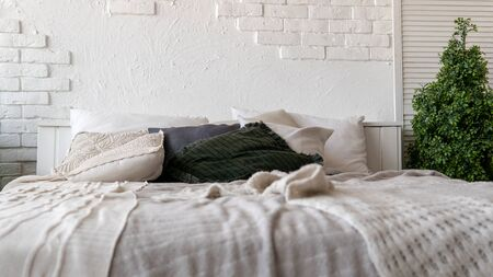 From above warm blanket and soft pillows placed on comfortable unmade bed in stylish contemporary bedroom