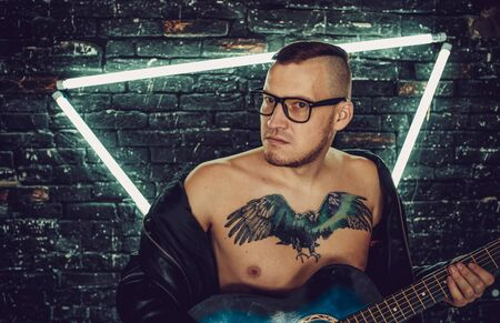 Stylish guy with bird tattoo on chest looking away and playing guitar while standing against shabby brick wall with triangle illumination