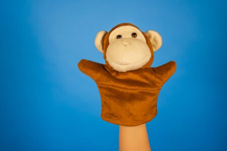 Concept of puppet show. Close-up of hand with puppet monkey.