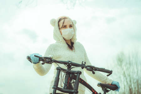 Portrait of young woman in medical mask and gloves with bicycle against sky. Adult female covering face to protect yourself from diseases on walk. Concept of threat of coronavirus epidemic infection. Stok Fotoğraf