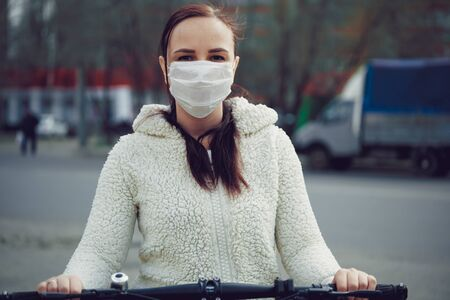 Young woman in medical mask stands with bicycle in city street. Adult female covered face with mask to protect yourself from diseases on walk. Concept of threat of coronavirus epidemic infection.
