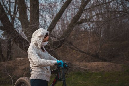 Young woman in medical mask and gloves stands with bicycle, holding on to rudder in countryside. Female protecting yourself from diseases on walk. Concept of threat of coronavirus epidemic infection. Banque d'images