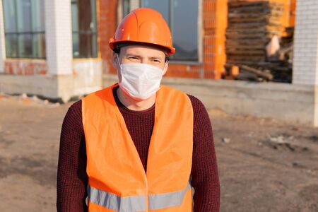 Portrait of male construction worker in medical mask and overalls on background of house under construction.