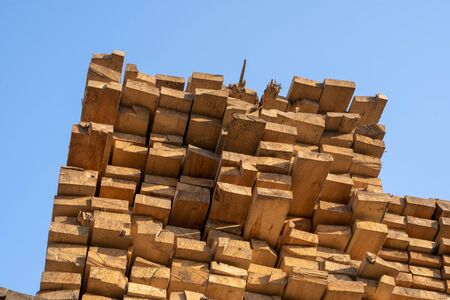 Wooden boards, lumber, industrial wood, timber. Pine wood timber stack of natural rough wooden boards on building site. Industrial timber building materials