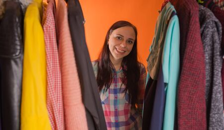 Young woman grimacing standing between clothes in wardrobe. Adult female choosing things in store.