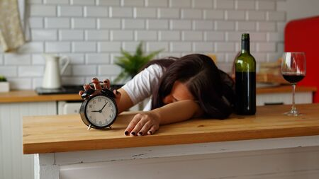 An alcoholic woman sleeps in the kitchen in the morning, near a bottle of wine. Concept: Hangover 版權商用圖片