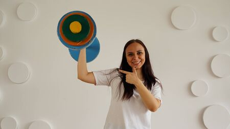 Young woman lifts multicolored barbell against white patterned wall. Adult lady doing sport, using all her strength
