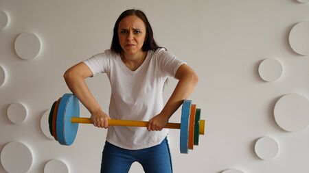 Young woman lifts multicolored barbell against white patterned wall. Adult lady doing sport, using all her strength. Imagens