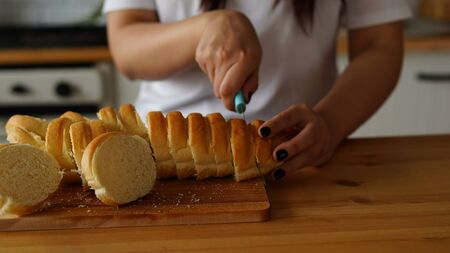 Women's hands cutting baguette with knife on chopping board on kitchen table.