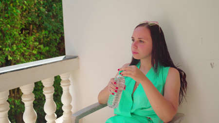 A beautiful young woman is sitting on a chair and drinking a cold water from a bottle on the terrace. Stok Fotoğraf
