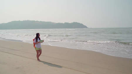 Traveling young woman with backpack walking along sea coast. Female tourist reading and examining map while resting on sandy beach near waving sea.