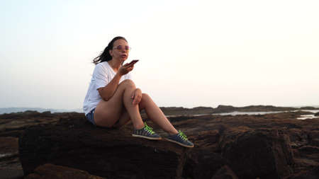 Relaxed woman sitting on stone and recording audio message on smartphone on shore. Side view of pleasant girl spending time enjoying vacation and talking on mobile phone on stony shore. Stok Fotoğraf
