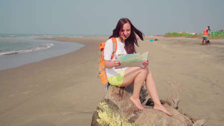 A traveling young woman is sitting on a log and looking at the map by the sea or ocean in a bright sunny day