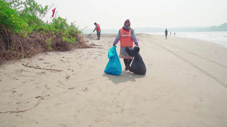 Morjim, India December 14, 2019: Cleaners establish order on seacoast from garbage. Workers make clean sandy beach for comfortable stay for tourists.