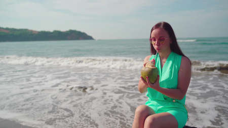 A beautiful young woman is sitting on a log and drinking the coconut by the sea or ocean in a bright sunny day.