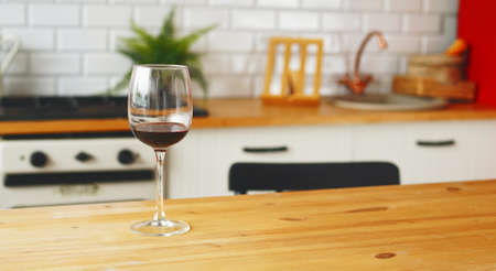 Close up of glass of wine on table in kitchen.