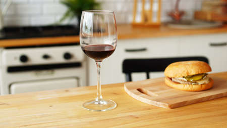 Close up of glass of wine with burger on wooden board Stok Fotoğraf
