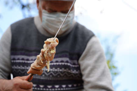 Mature man in medical mask impales raw shashlik on skewer. Older male holds skewer with barbecue.