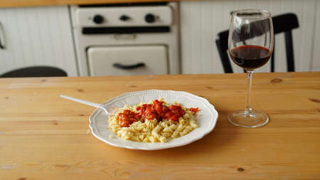 Close up of dish in white plate with glass of wine on table in kitchen Stok Fotoğraf