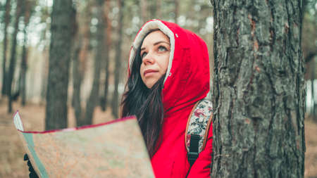 A traveling woman with map in woods. A portrait of the pretty woman with a backpack, standing near a tree in a cold weather Stok Fotoğraf