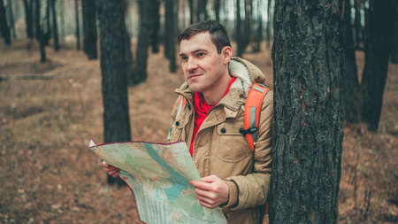 A traveling man with map in woods. A portrait of the handsome man with a backpack, standing near a tree in a cold weather