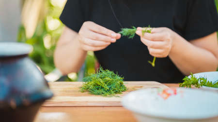 Close up of women's hands plucks greens from sticks and puts them on cutting board Stok Fotoğraf