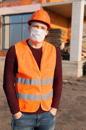 Portrait of male construction worker in medical mask and overalls