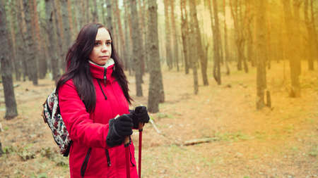 A pretty young woman is engaged in the nordic walking in woods Stok Fotoğraf