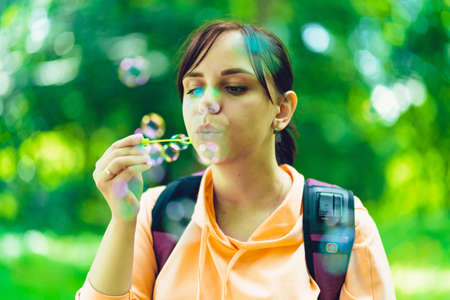 Young woman blowing bubbles on nature. Stok Fotoğraf