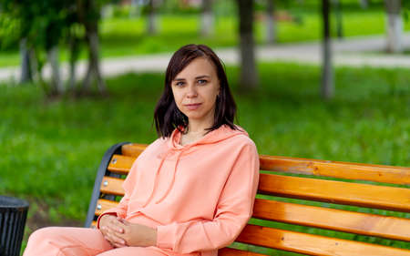 Young woman sits on bench in park. Adult female enjoys her rest on fresh air.