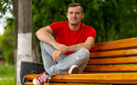 Adult male in red t shirt and jeans sitting on bench and looking away while resting in park on summer day 写真素材