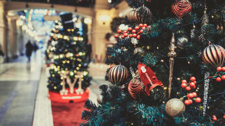 Close up of part of Christmas tree with different christmas toys and garland in shopping center. Coniferous tree with decorative adornments to create festive mood during holiday celebration.
