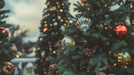 Close up of part of Christmas tree with different christmas toys and garland on street in evening city. Coniferous tree with decorative decorations to create festive mood