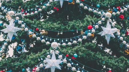Close up of big Christmas tree with different christmas toys and decorative adornments on street. Coniferous tree with garland, beads and stars to create festive mood during holiday celebration. Фото со стока