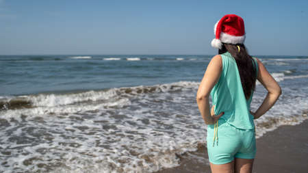 Rear view of young woman in Santa Claus hat, standing on seashore and looking into distance on sunny day. Adult brunette in Christmas hat celebrating new year's holidays near waving sea on resort