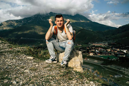 Young man grimaces, sitting on stone on background of village in mountains. Tired male tourist aping, resting on hill after active trekking in mountains.