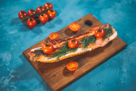 Still-life of appetizing bruschetta on wooden board. Close up of sandwich with melted cheese, bacon, cherry tomatoes and dill on blue background