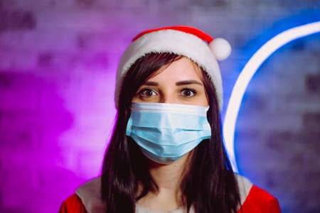 Young woman in medical mask and Santa Claus suit against illuminated wall. Close up of brunette in Christmas hat and protective mask. Concept of safe Christmas celebration during coronavirus pandemic.