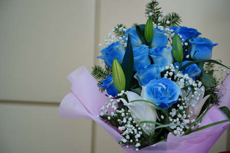 Close up of colorful bouquet of flowers. Flower composition of blue roses and white lilies in wrapping paper