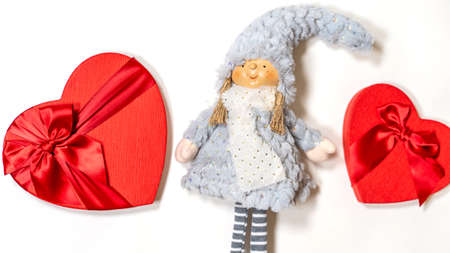 Close up of cute doll with gift boxes in form of heart on isolated white background. Concept of holidays, presents and good mood